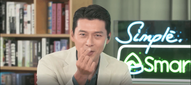Hyun Bin gives his fans a finger heart sign to show his love.
